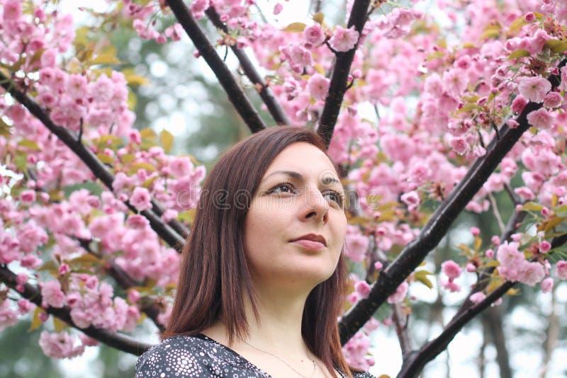Retrato de una mujer joven hermosa linda en el jard?n de la primavera en el fondo de Sakura floreciente imagen de archivo libre de regalías