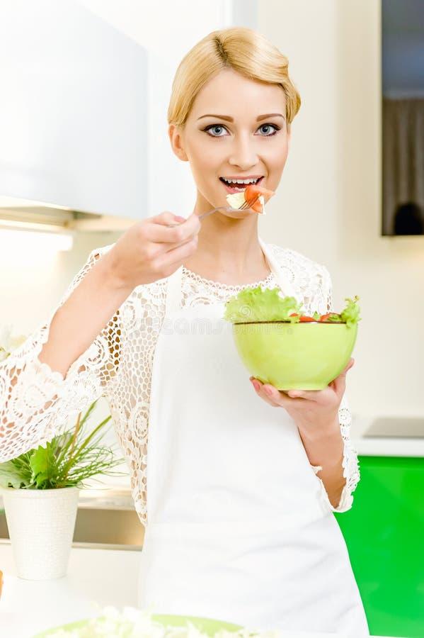 Retrato de una mujer joven hermosa que come la ensalada vegetal fotos de archivo libres de regalías