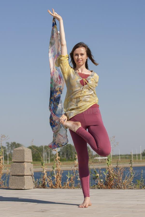 Retrato de una mujer joven hermosa que se sienta en actitud de la yoga en la playa imagen de archivo libre de regalías