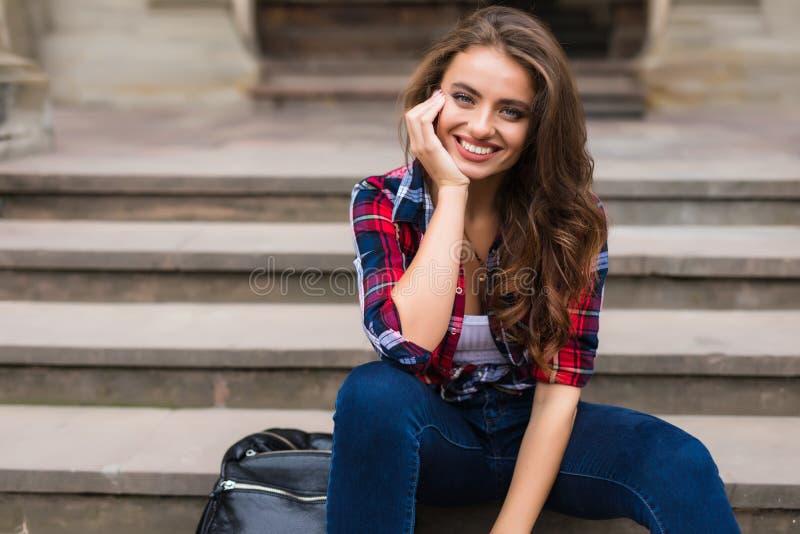 Retrato de una mujer joven hermosa que se sienta en la sonrisa hermosa de la mujer joven de las escaleras al aire libre fotos de archivo