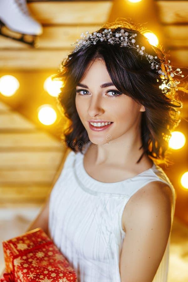 Retrato de una mujer joven hermosa que sostiene un regalo por Año Nuevo y la Navidad foto de archivo