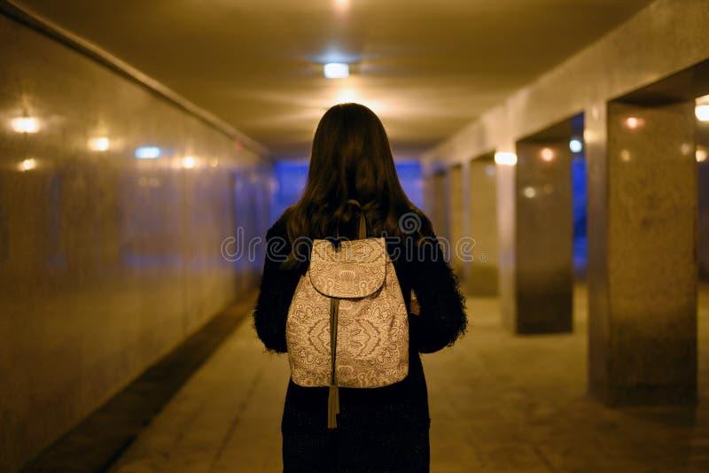 Retrato de una mujer joven de la parte posterior con una mochila ligera en la parte posterior en el paso de peatones subterráneo  fotos de archivo
