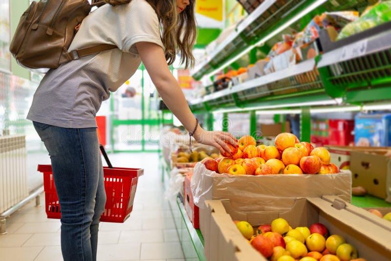 Retrato de una mujer joven linda con una cesta en sus manos, que elige manzanas en el supermercado imagen de archivo