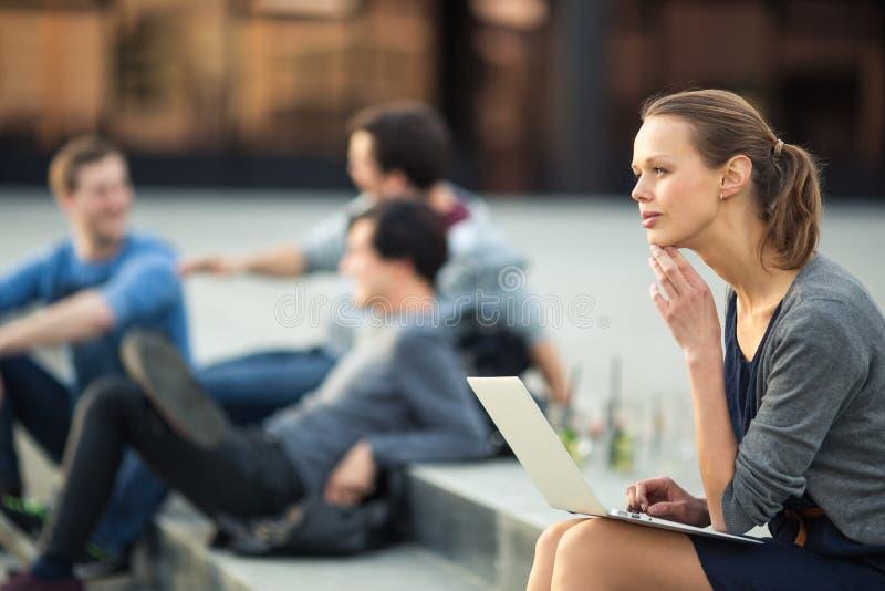 Retrato de una mujer joven lisa, usando el ordenador portátil, estando pensativo en contexto urbano/de la ciudad foto de archivo