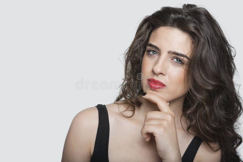 Retrato de una mujer joven pensativa con la mano en la barbilla sobre fondo gris imagenes de archivo