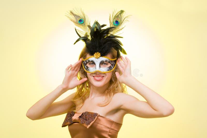 Retrato de una mujer joven que desgasta una máscara del carnaval fotografía de archivo libre de regalías