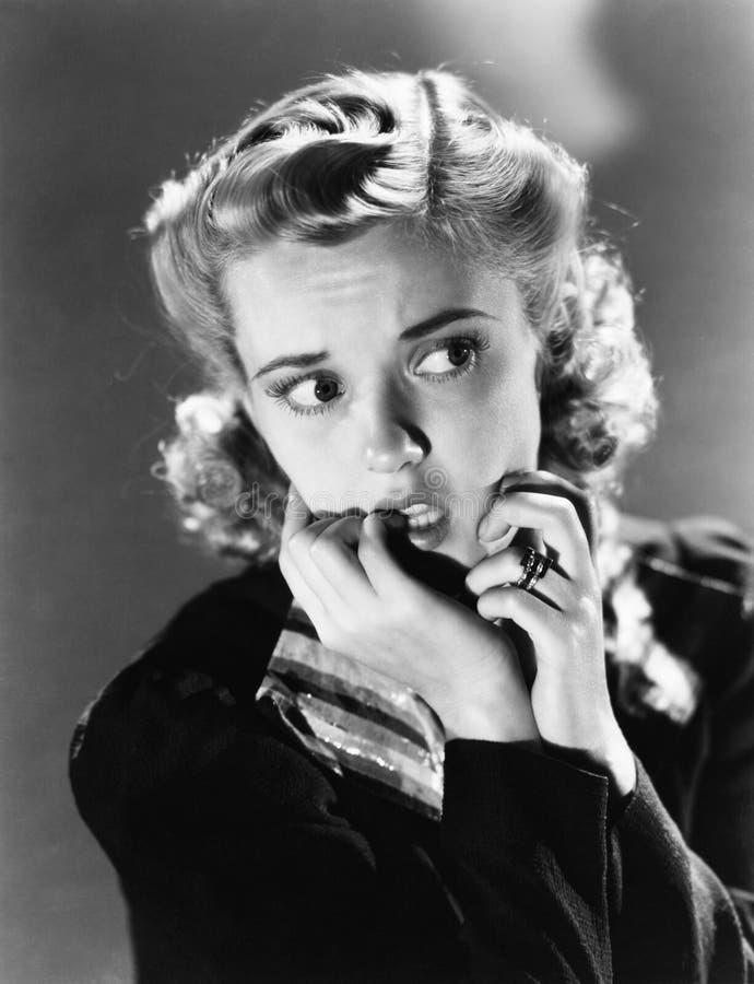 Retrato de una mujer joven que muerde su clavo y que parece asustada (todas las personas representadas no son vivas más largo y n fotografía de archivo libre de regalías