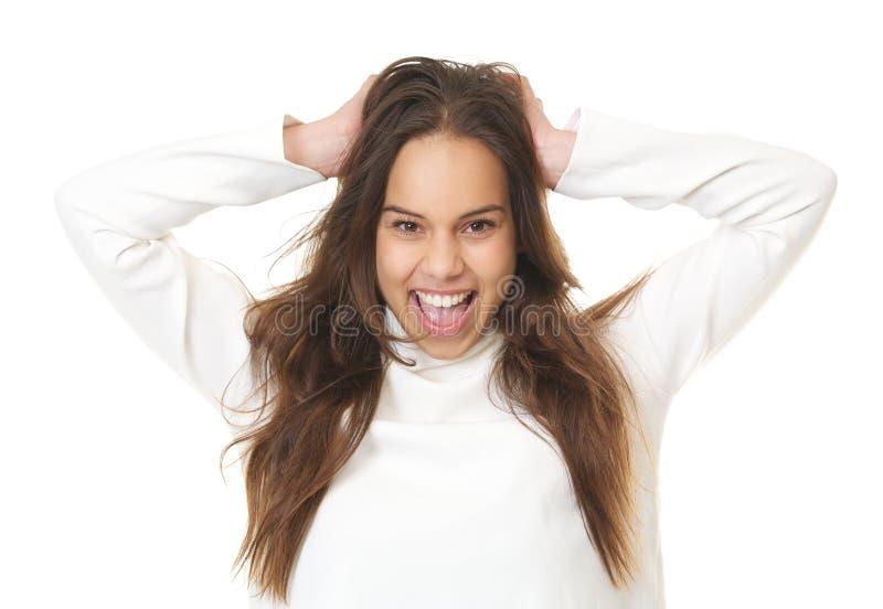 Retrato de una mujer joven que ríe con las manos en pelo fotografía de archivo libre de regalías