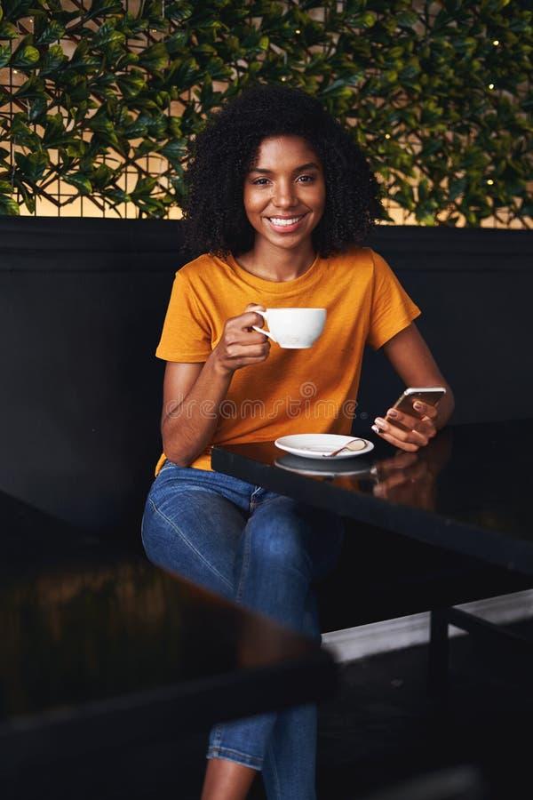 Retrato de una mujer joven que se sienta en café con smartphone imagenes de archivo