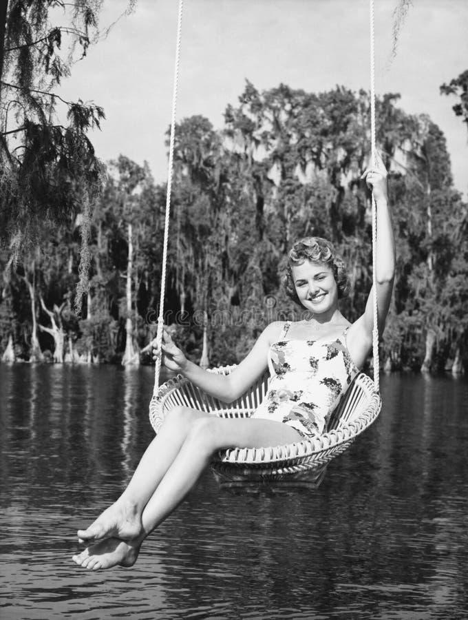 Retrato de una mujer joven que se sienta en un oscilación en la orilla del lago y sonrisa (todas las personas representadas no so fotos de archivo libres de regalías