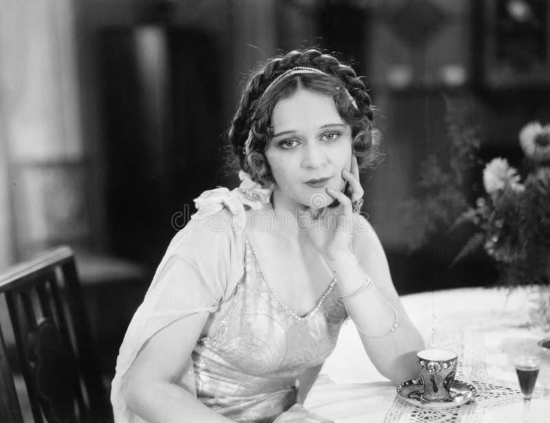 Retrato de una mujer joven que se sienta en una tabla y que piensa en un restaurante (todas las personas representadas no son viv imágenes de archivo libres de regalías