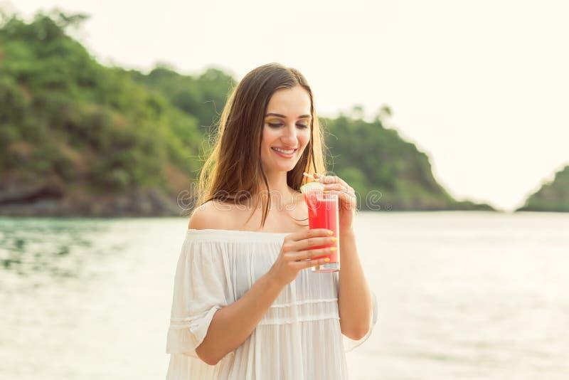 Retrato de una mujer joven que sostiene un cóctel fresco de la sandía en la playa tropical imágenes de archivo libres de regalías