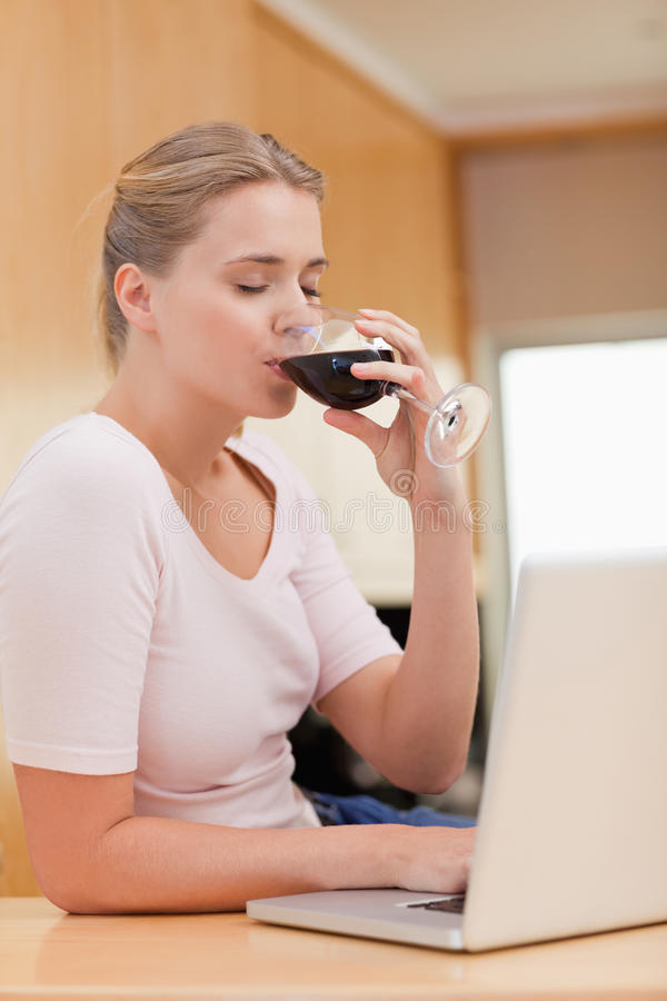 Retrato de una mujer joven que usa una computadora portátil mientras que bebe el vino rojo fotografía de archivo libre de regalías