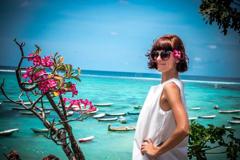 Retrato de una mujer joven sana hermosa cerca del océano con agua azul y las flores Isla tropical Bali, Indonesia fotografía de archivo