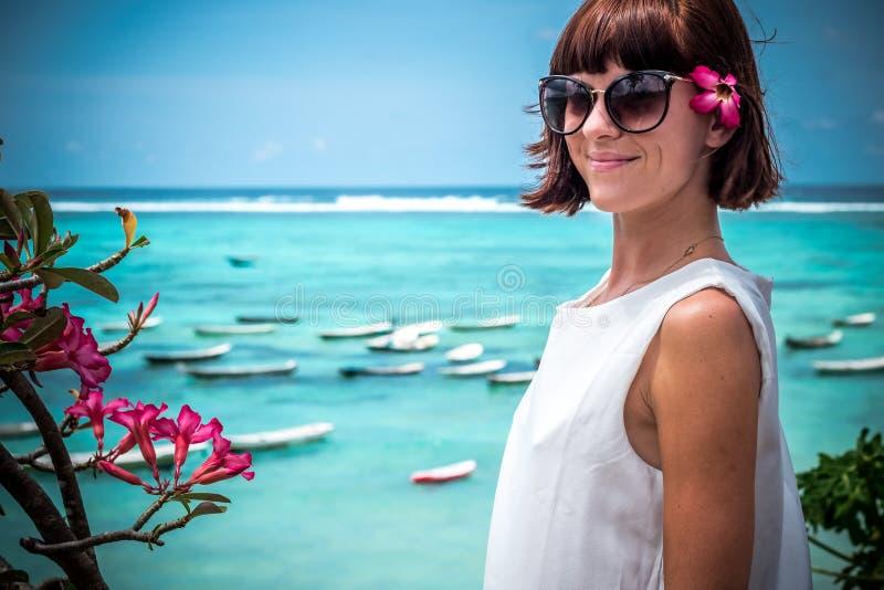 Retrato de una mujer joven sana hermosa cerca del océano con agua azul y las flores Isla tropical Bali, Indonesia foto de archivo