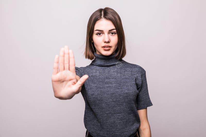 Retrato de una mujer joven seria que se coloca con gesto extendido de la parada de la demostración de la mano sobre el fondo blan imagen de archivo
