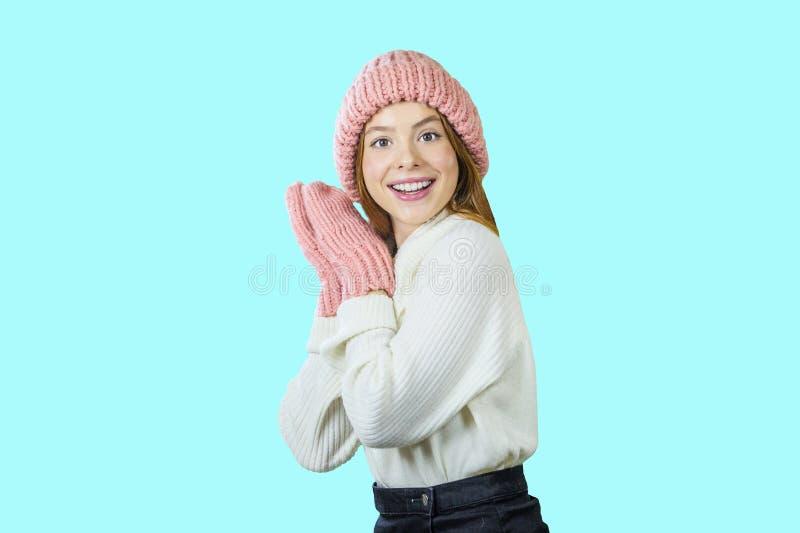 Retrato de una mujer joven sonriente que lleva el sombrero y la bufanda rosados Mujer sonriente feliz en fondo de la turquesa en  fotos de archivo