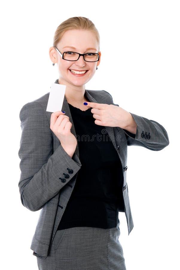 Retrato de una mujer joven sonriente que señala en la tarjeta en blanco en ella fotos de archivo