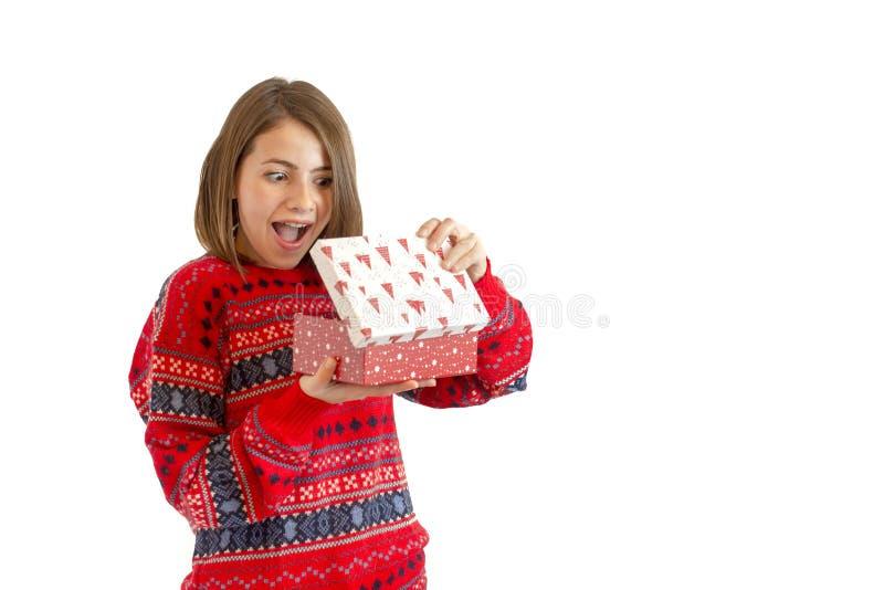 Retrato de una mujer linda feliz que sostiene la caja de regalo aislada en un fondo blanco foto de archivo