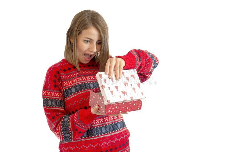 Retrato de una mujer linda feliz que sostiene la caja de regalo aislada en un fondo blanco imagenes de archivo