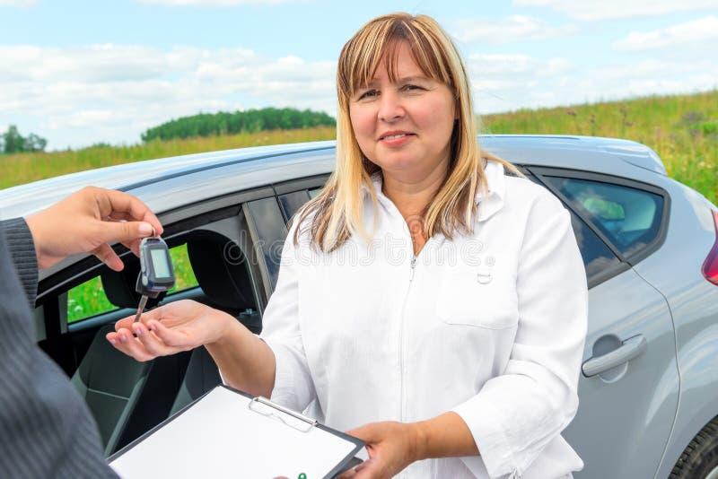 Retrato de una mujer madura con un nuevo coche fotografía de archivo libre de regalías