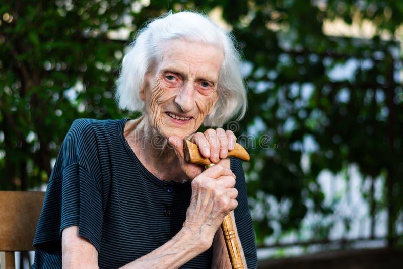 Retrato de una mujer mayor con un bastón que camina foto de archivo
