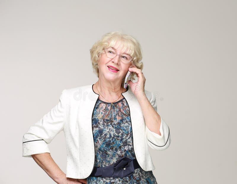 Retrato de una mujer mayor con un teléfono celular imagen de archivo