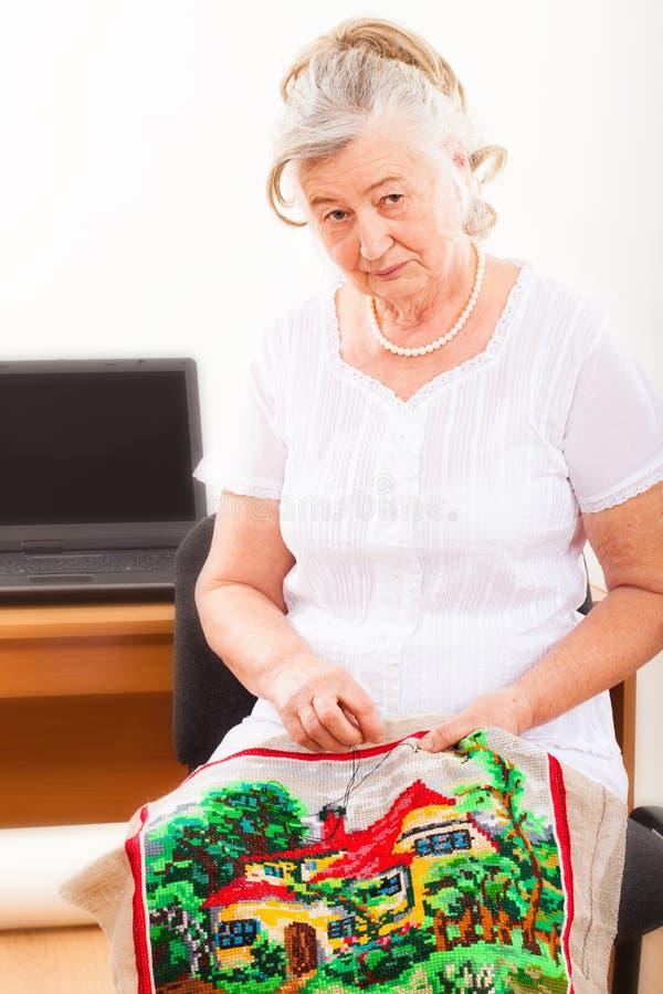 Retrato de una mujer mayor contratada a costura imagen de archivo