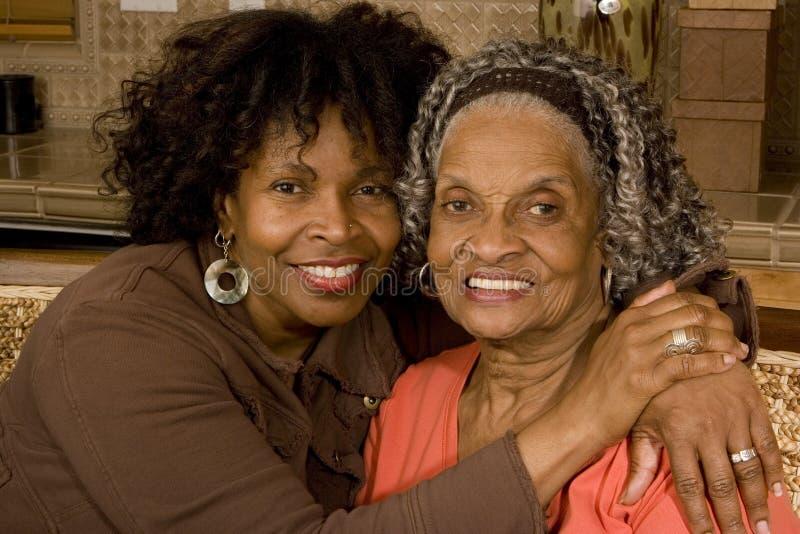 Retrato de una mujer mayor que abraza a su hija imagenes de archivo
