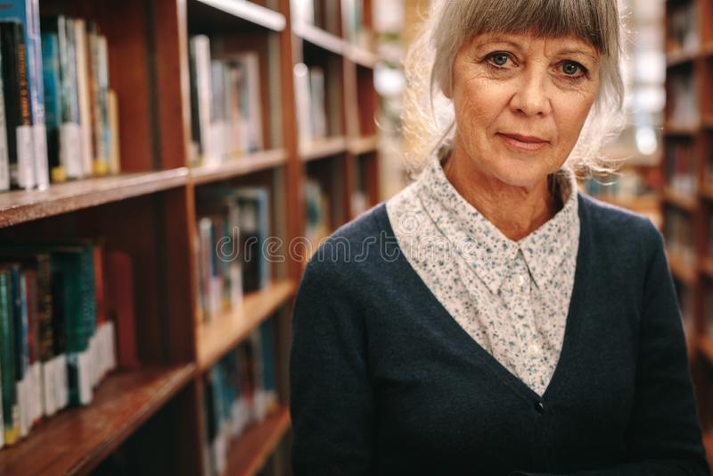 Retrato de una mujer mayor que se coloca en una biblioteca fotografía de archivo libre de regalías
