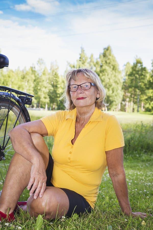 Retrato de una mujer mayor sonriente que se sienta en el parque con la bicicleta imagen de archivo