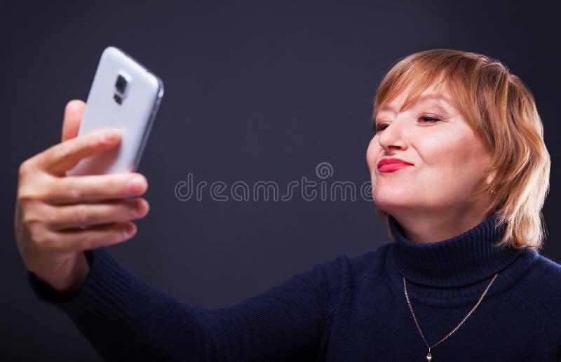 Retrato de una mujer de mediana edad que hace la foto del selfie con smartphone en un fondo negro imagenes de archivo