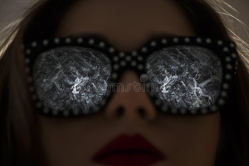 Retrato de una mujer morena atractiva y atractiva joven con el lápiz labial rojo en vestido y gafas de sol negros foto de archivo