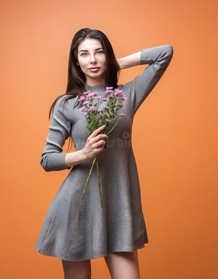 Retrato de una mujer morena hermosa joven en el vestido gris que sostiene las flores violetas en sus manos y que mira la cámara imagen de archivo libre de regalías