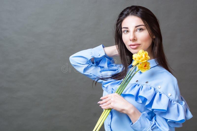 Retrato de una mujer morena hermosa joven en la camisa azul que sostiene las flores amarillas en sus manos y que mira la cámara fotos de archivo libres de regalías