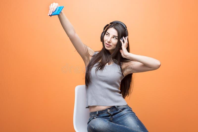 Retrato de una mujer morena sonriente joven en la ropa casual que hace un selfie con su teléfono azul contra fondo anaranjado fotos de archivo libres de regalías