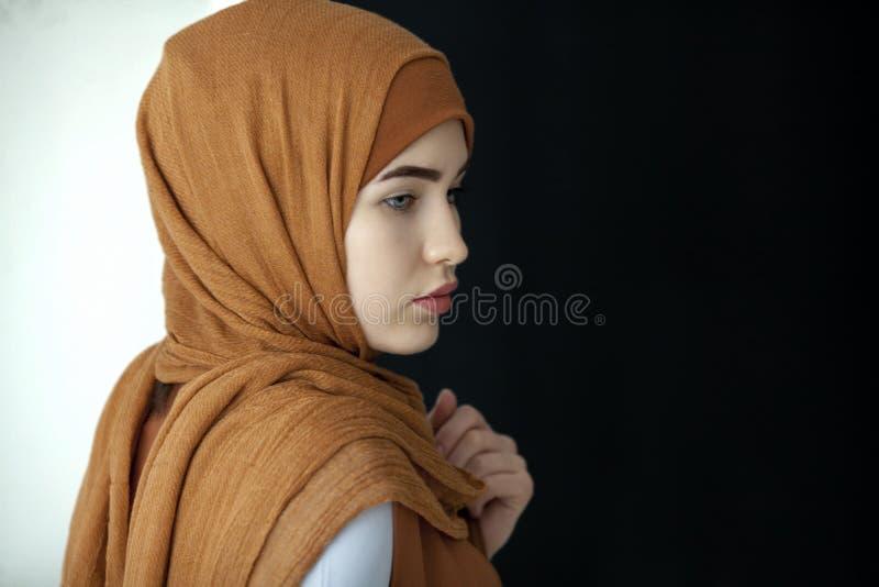 Retrato de una mujer musulmán hermosa en una bufanda verde que cubre su cabeza fotografía de archivo