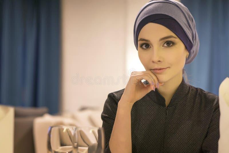 Retrato de una mujer musulmán hermosa en una tabla en un café imagen de archivo