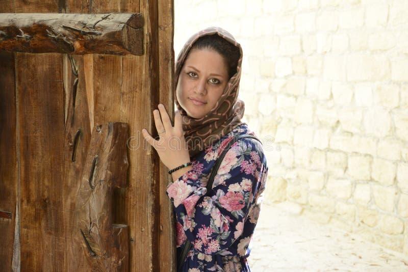 Retrato de una mujer musulmán joven detrás de la puerta de madera fotografía de archivo