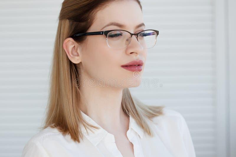Retrato de una mujer de negocios elegante joven en una camisa blanca y vidrios imágenes de archivo libres de regalías