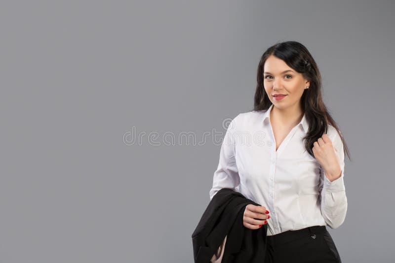 Retrato de una mujer de negocios joven hermosa que se coloca con la mano que sostiene la chaqueta detrás de su hombro contra gris fotos de archivo