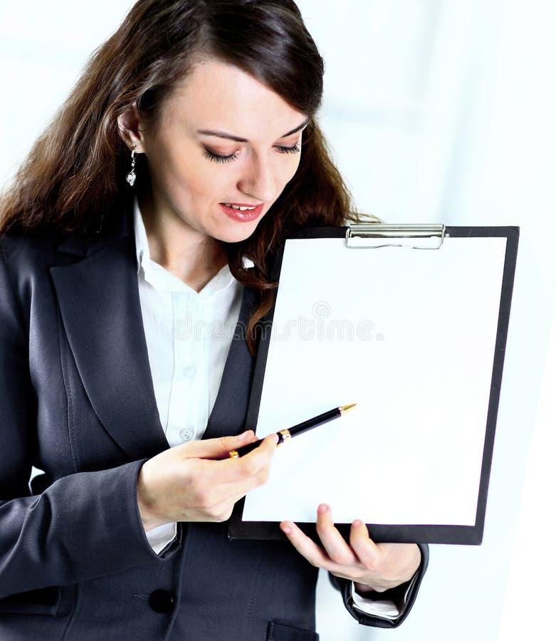 Retrato de una mujer de negocios joven linda con el plan de trabajo que sonríe en oficina imagen de archivo