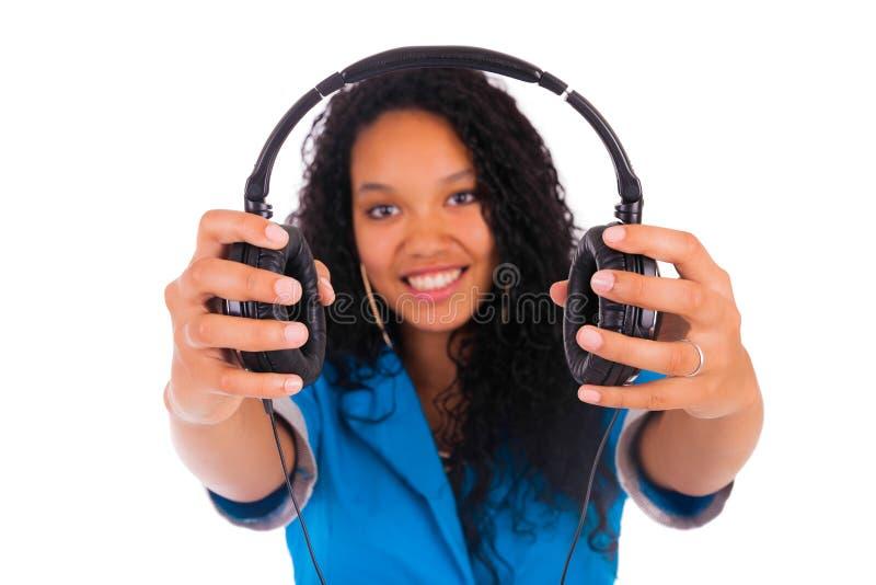 Retrato de una mujer negra hermosa con los auriculares que escucha foto de archivo