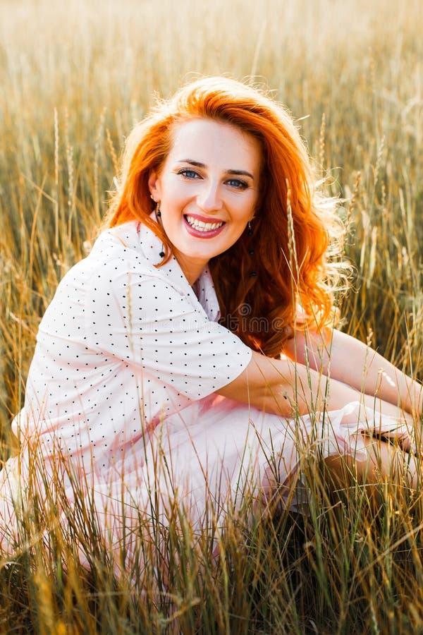 Retrato de una mujer pelirroja joven en una hierba amarilla alta en la puesta del sol imagen de archivo libre de regalías