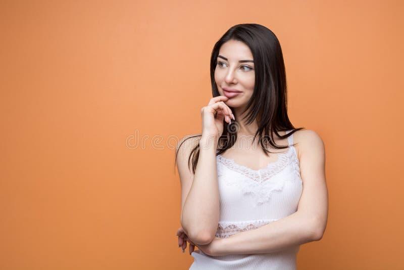 Retrato de una mujer pensativa morena hermosa joven que lleva a cabo su mano nueva su barbilla y que mira a un lado imagen de archivo