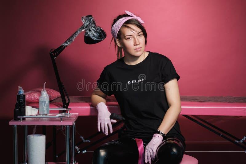 Retrato de una mujer profesional del amo del tatuaje Ropa negra, y dreadlocks Fondo rojo, rosado y blanco Lugar de imágenes de archivo libres de regalías