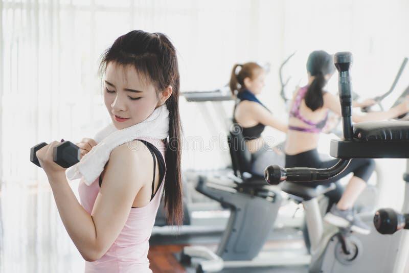 Retrato de una mujer que lleva a cabo pesa de gimnasia en club de fitness fotografía de archivo