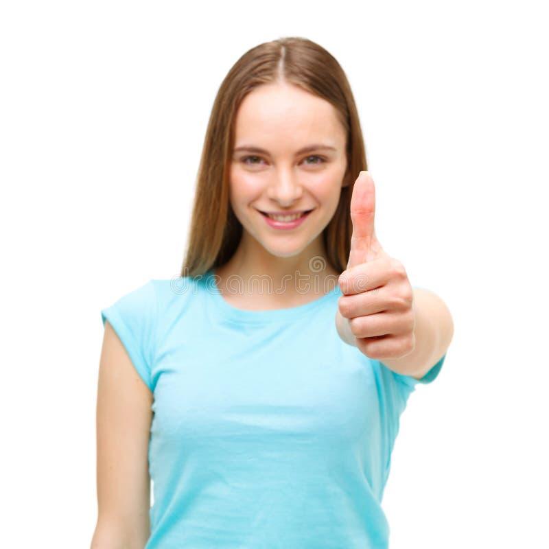 Retrato de una mujer que muestra los pulgares encima de la muestra y de la sonrisa aisladas imagen de archivo