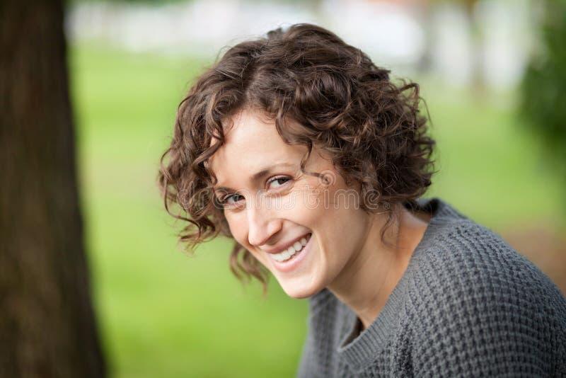 Retrato de una mujer que sonríe en la cámara Ella es feliz en el parque imagenes de archivo