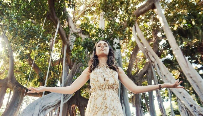 Retrato de una mujer relajada que presenta sobre la selva tropical foto de archivo